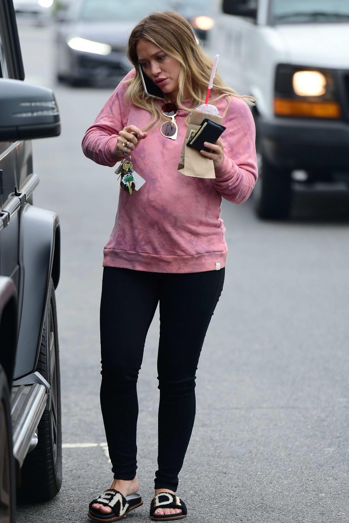 Hilary Duff seen wearing a pink sweatshirt and Fendi flip flops as she grabs a breakfast smoothie in Los Angeles
