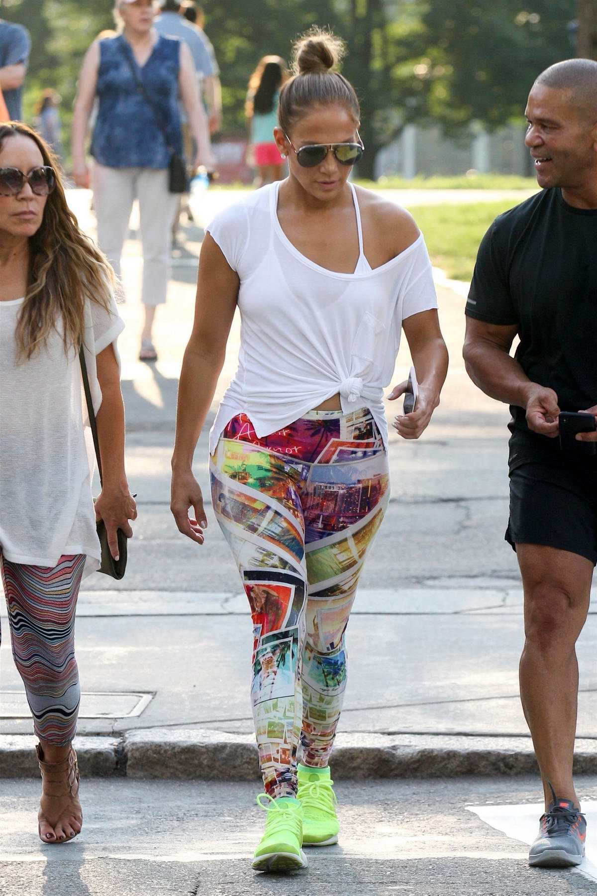 Jennifer Lopez wears white t-shirt, colorful graphic leggings with neon green trainers as she steps out in Boston, Massachusetts