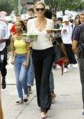 Karlie Kloss plays CEO morning 'Coffee Girl' carrying two trays of drinks for her Kode With Klossy staff in New York City