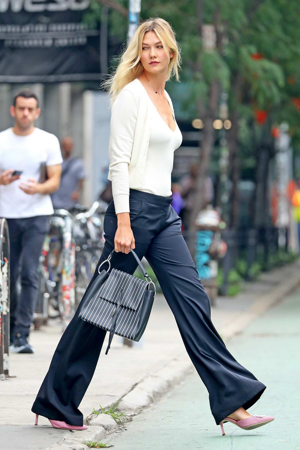 Karlie Lloss steps out wearing a white plunging neckline top with navy trousers in New York City