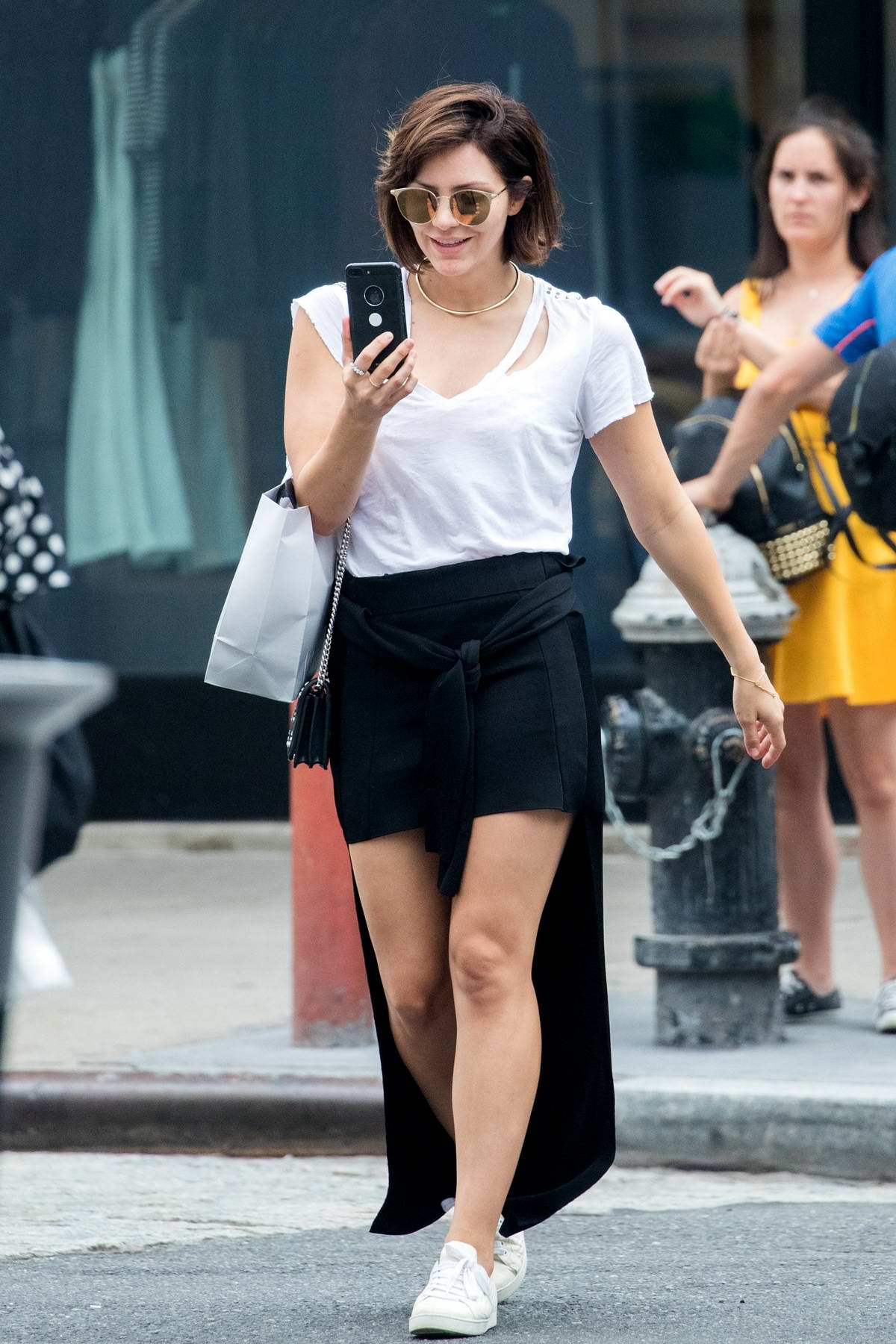Katharine McPhee is color-coordinated in a white top, short black skirts with white sneakers as she steps out for shopping in New York City