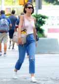 Katie Holmes seen wearing light pink top and blue jeans with a pair of sunglasses while out in New York City