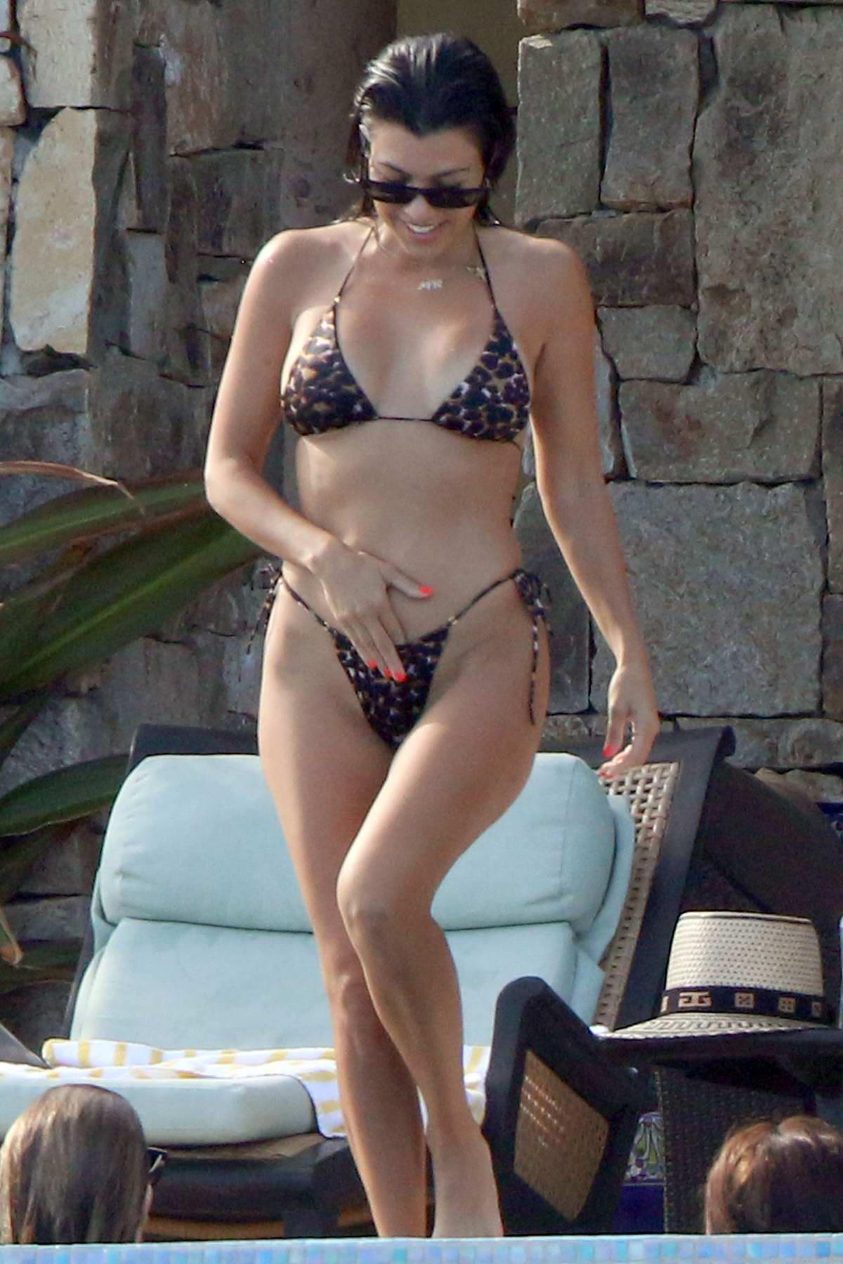 Kourtney Kardashian wears a leopard print bikini while she relax by the pool in Cabo, Mexico