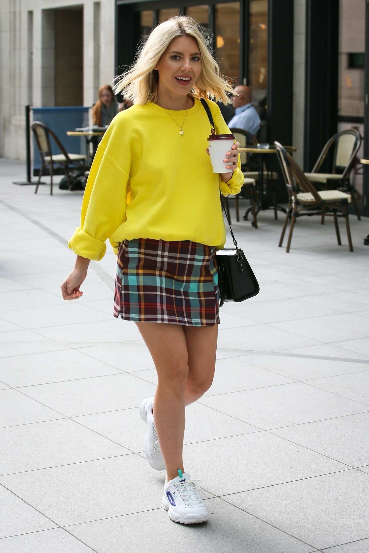 Mollie King wears a yellow sweater and a plaid mini skirt as she arrives at the BBC Radio One studios in London, UK