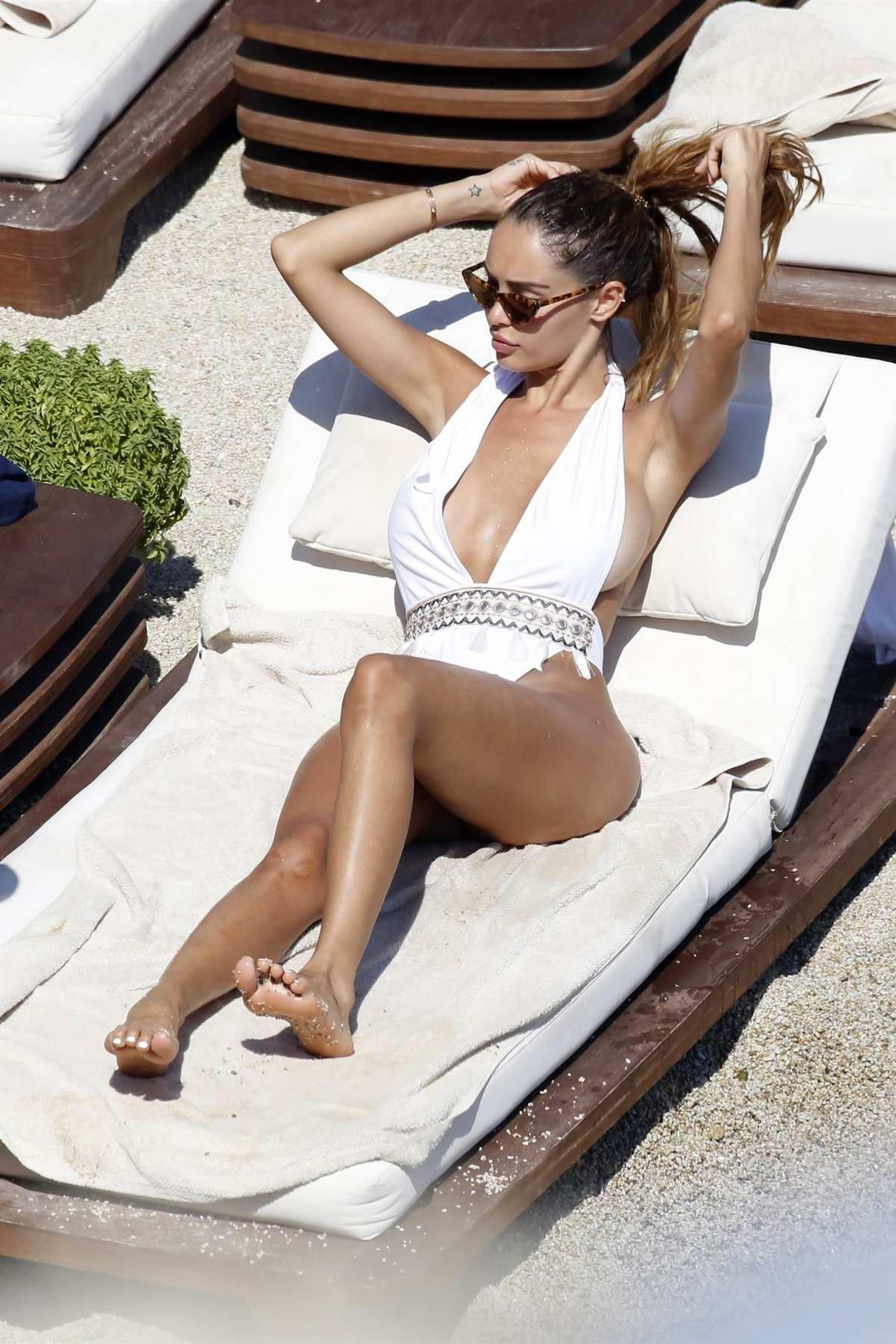 Nabilla Benattia wears a white swimsuit as she catch some sun on the beach in Mykonos, Greece
