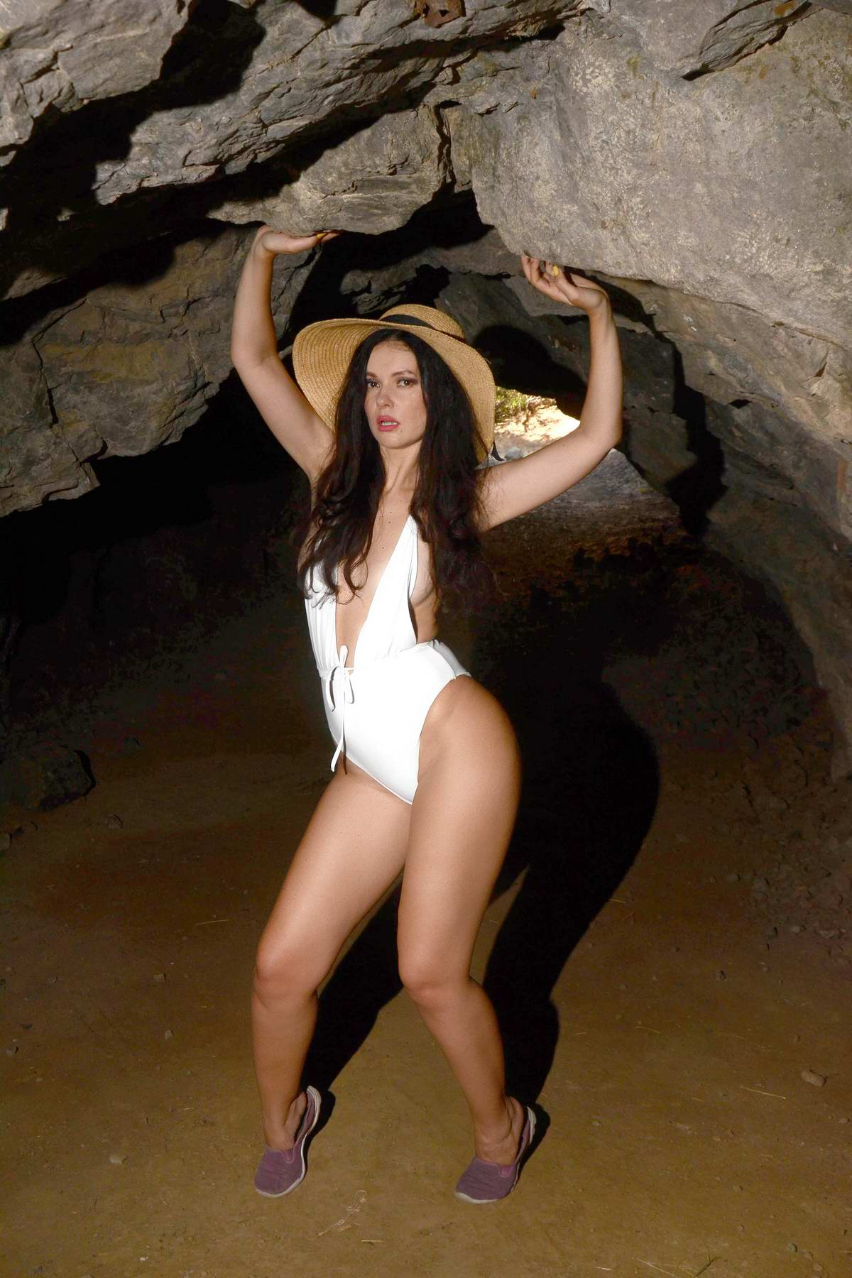 Natasha Blasick sports a white swimsuit and sunhat during a cave photoshoot in Los Angeles