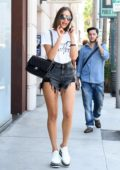 Olivia Culpo wears white t-shirt with a pair of denim shorts and sneakers while out shopping in Los Angeles