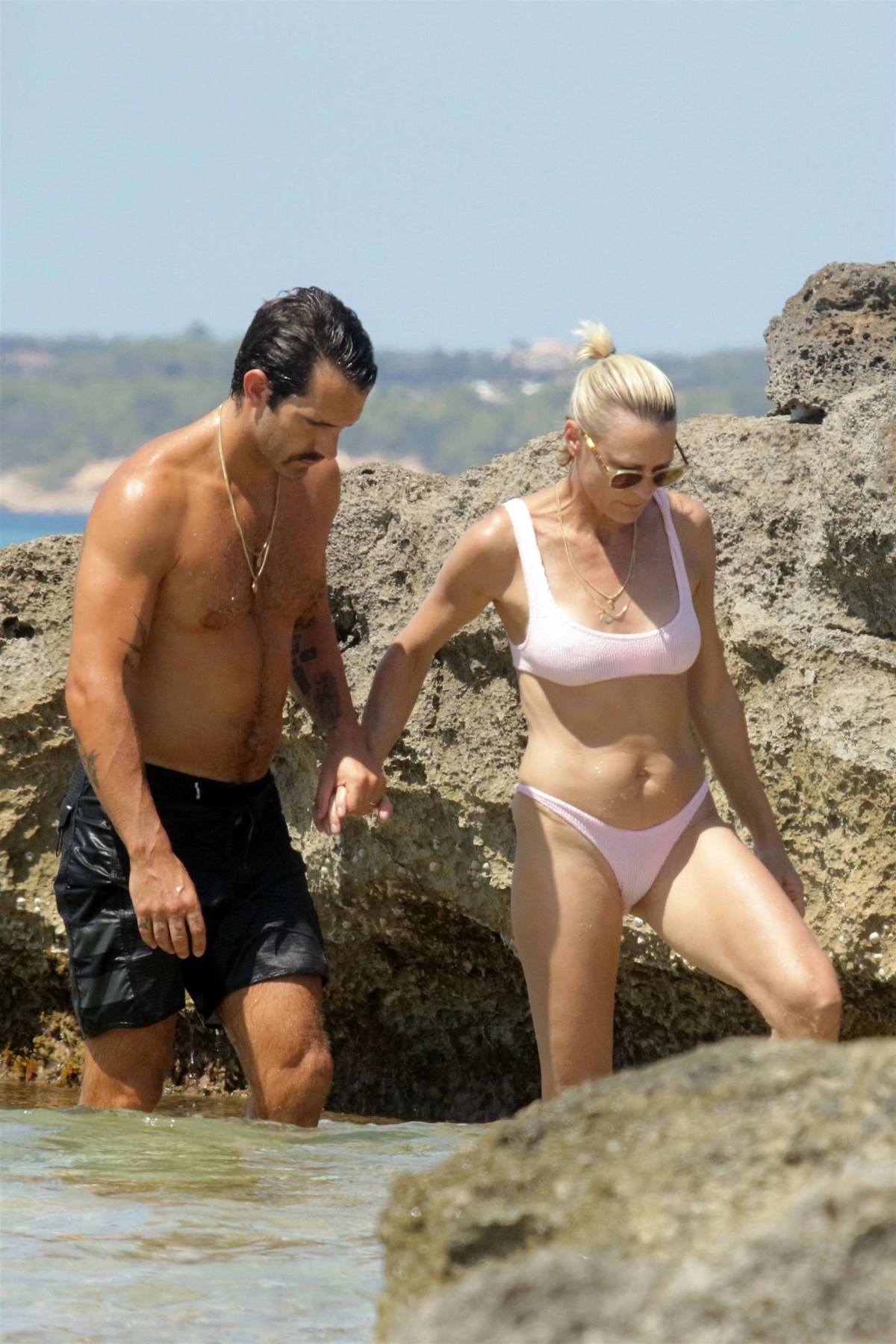 Robin Wright spotted in a light pink bikini as she gets in some PDA with husband Clement Giraudet while at the beach in Formentera, Spain