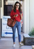 Alessandra Ambrosio rocks a red hoodie with skinny jeans and sneakers as she leaves a skincare clinic in Los Angeles