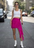Alessandra Ambrosio steps out in a white tank top with a bright pink skirt during Milan Fashion Week in Milan, Italy