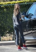 Alexis Ren sports black t-shirt with black leggings and red sneakers as she leaves an office with her boyfriend in Los Angeles