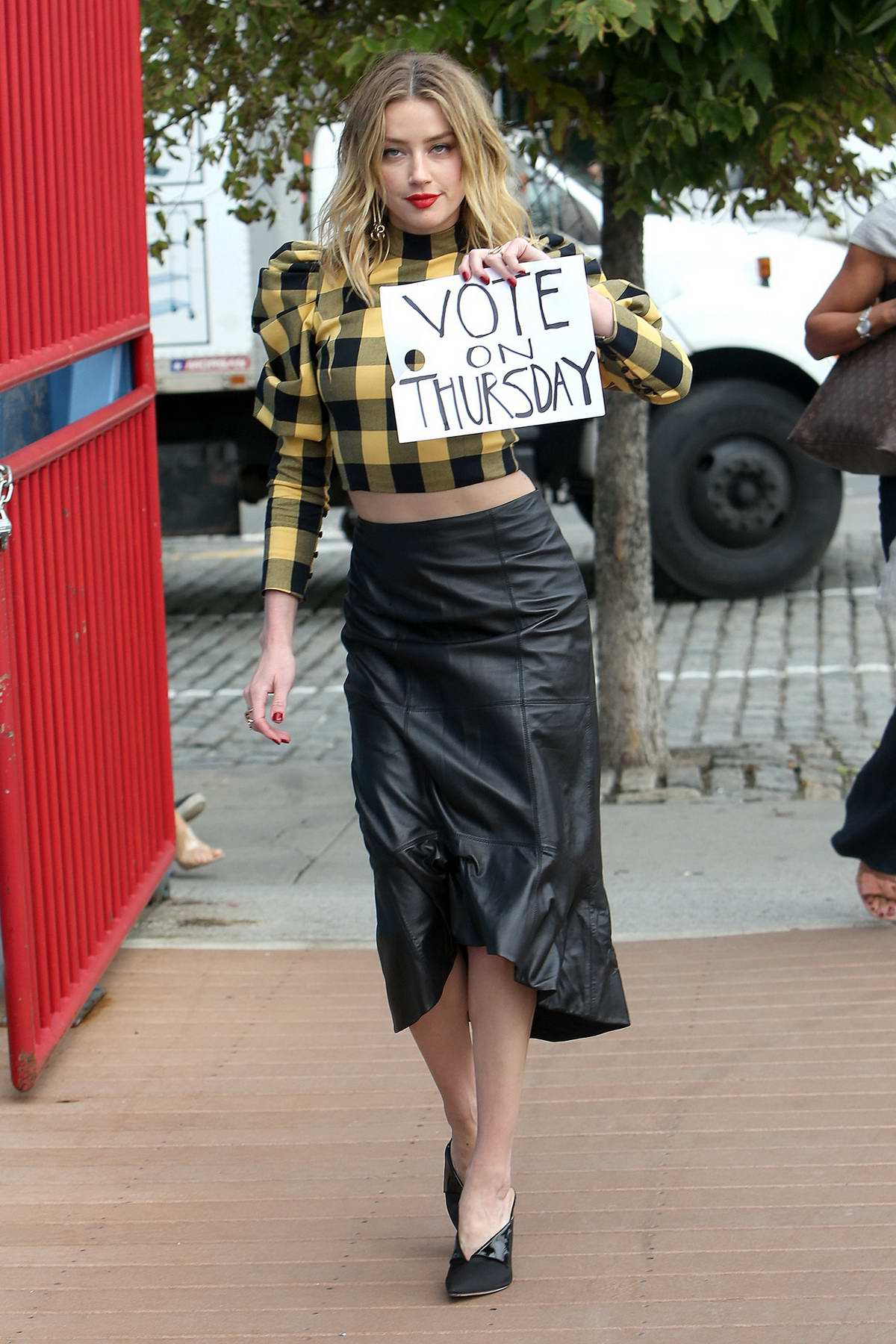 Amber Heard holds up a 'Vote' sign while arriving to a Fashion Show at Chelsea Pier in New York City