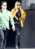 Ashley Benson sports an all black outfit with a yellow sweater while out in Los Angeles