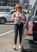 Ashley Tisdale wearing a white tank top, leggings with pink sneakers as she walks back to her car after a workout session in Los Angeles