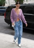 Bella Hadid wore a purple cardigan and jeans with white boots as she arrived at her apartment in New York City