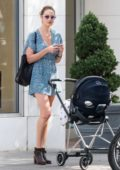 Candice Swanepoel wears a blue romper dress while out for a stroll with her baby in New York City