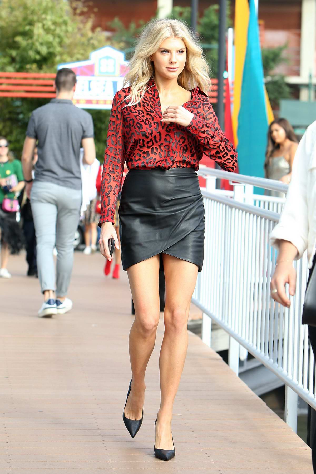Charlotte McKinney wearing a red animal print shirt with black leather skirt as she arrives at Chelsea Piers for the Alice+Olivia Show during New York Fashion Week in New York City