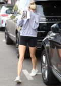 Charlotte McKinney wearing a sweatshirt and shorts as she leaves Kate Somerville covering her face in West Hollywood, Los Angeles