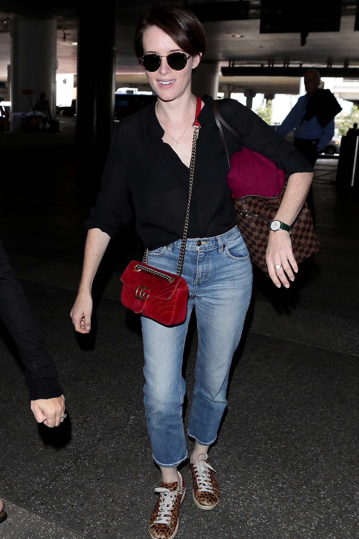 Claire Foy wears a black shirt and jeans with her Gucci purse as she arrives at LAX in Los Angeles