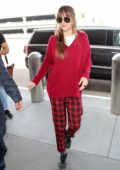 Dakota Johnson spotted in a red sweater with red and black checkered pants as she arrives at LAX airport in Los Angeles