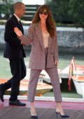 Dakota Johnson wears a plaid pantsuit while heading out during 75th Venice Film Festival in Venice, Italy