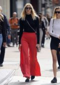 Devon Windsor wears a side split bright red flared pants and a black top while window shopping in SoHo, New York City