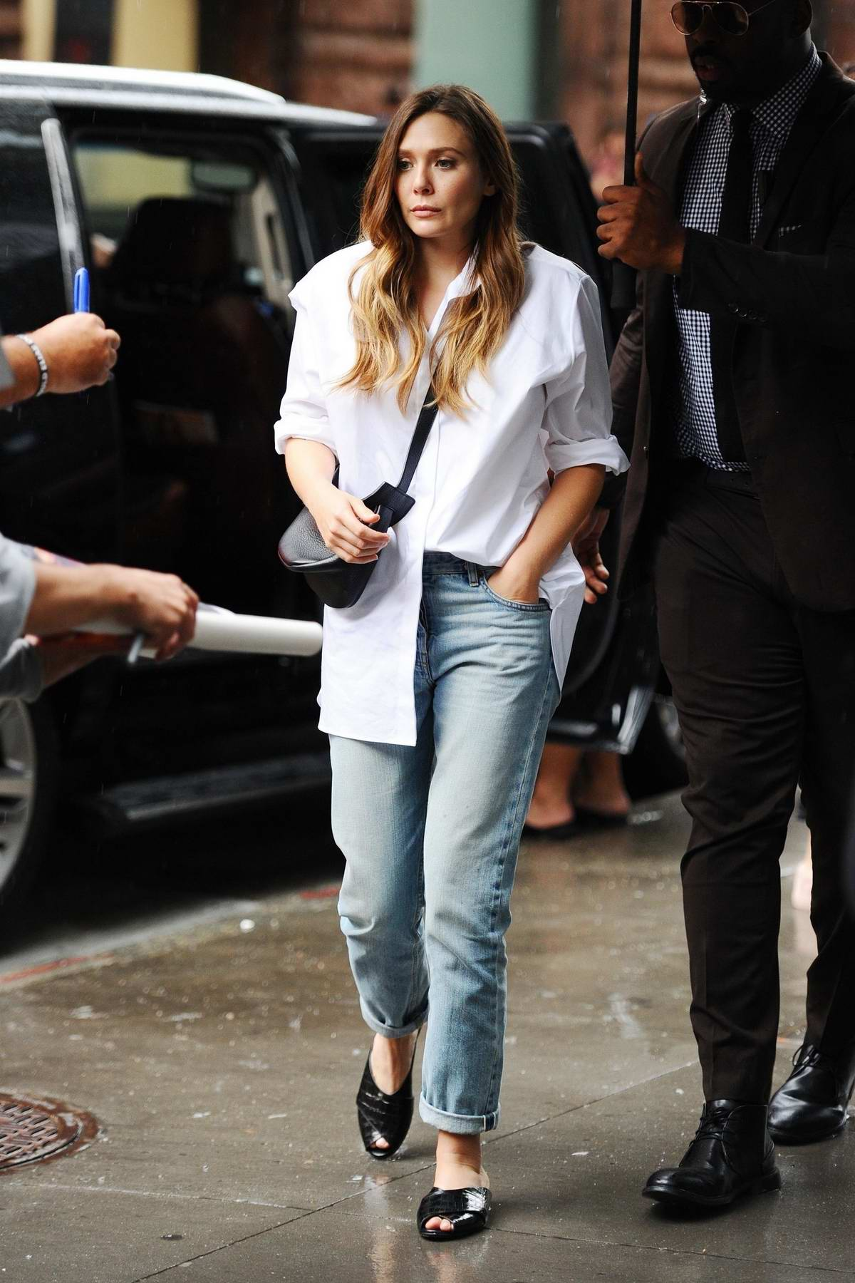 Elizabeth Olsen greets fans waiting in the rain at 'The Late Show With Stephen Colbert' in New York City