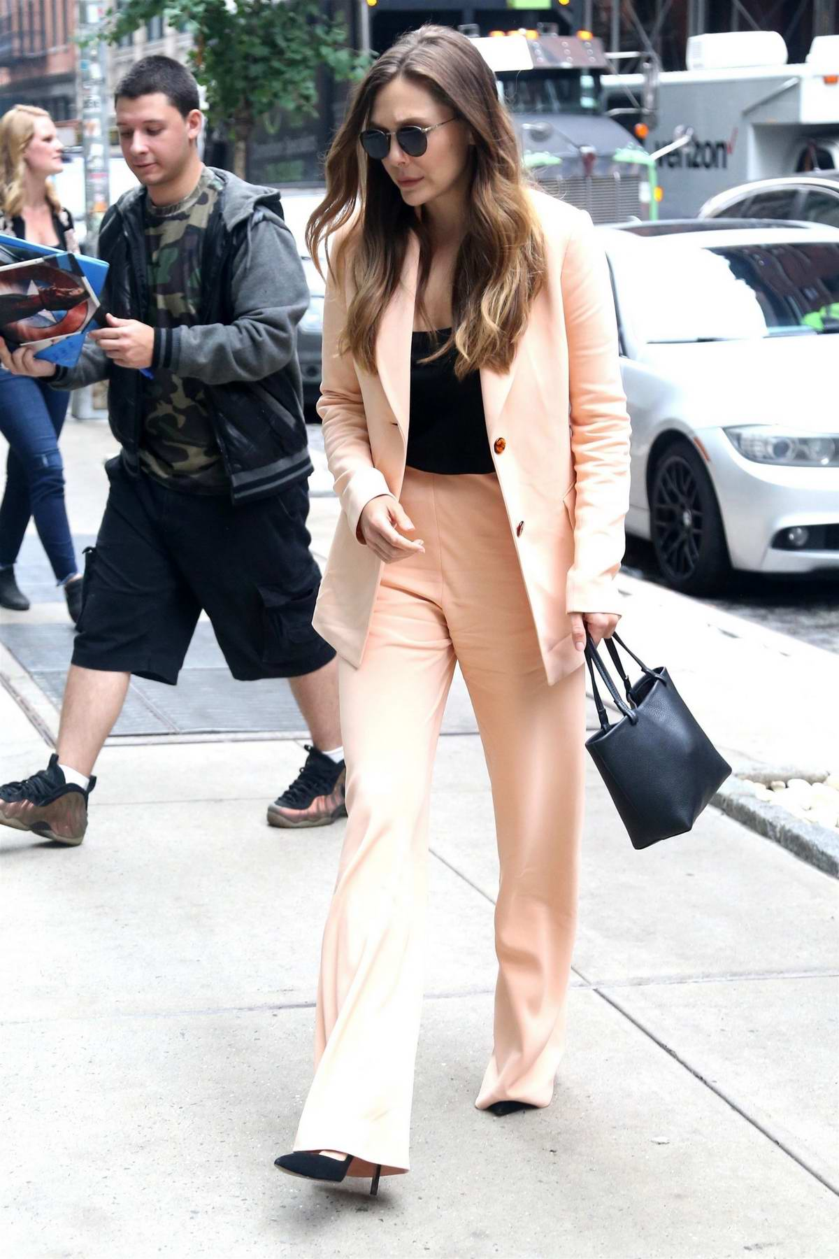 Elizabeth Olsen steps out in a pink pantsuit while stopping by an office building in New York City