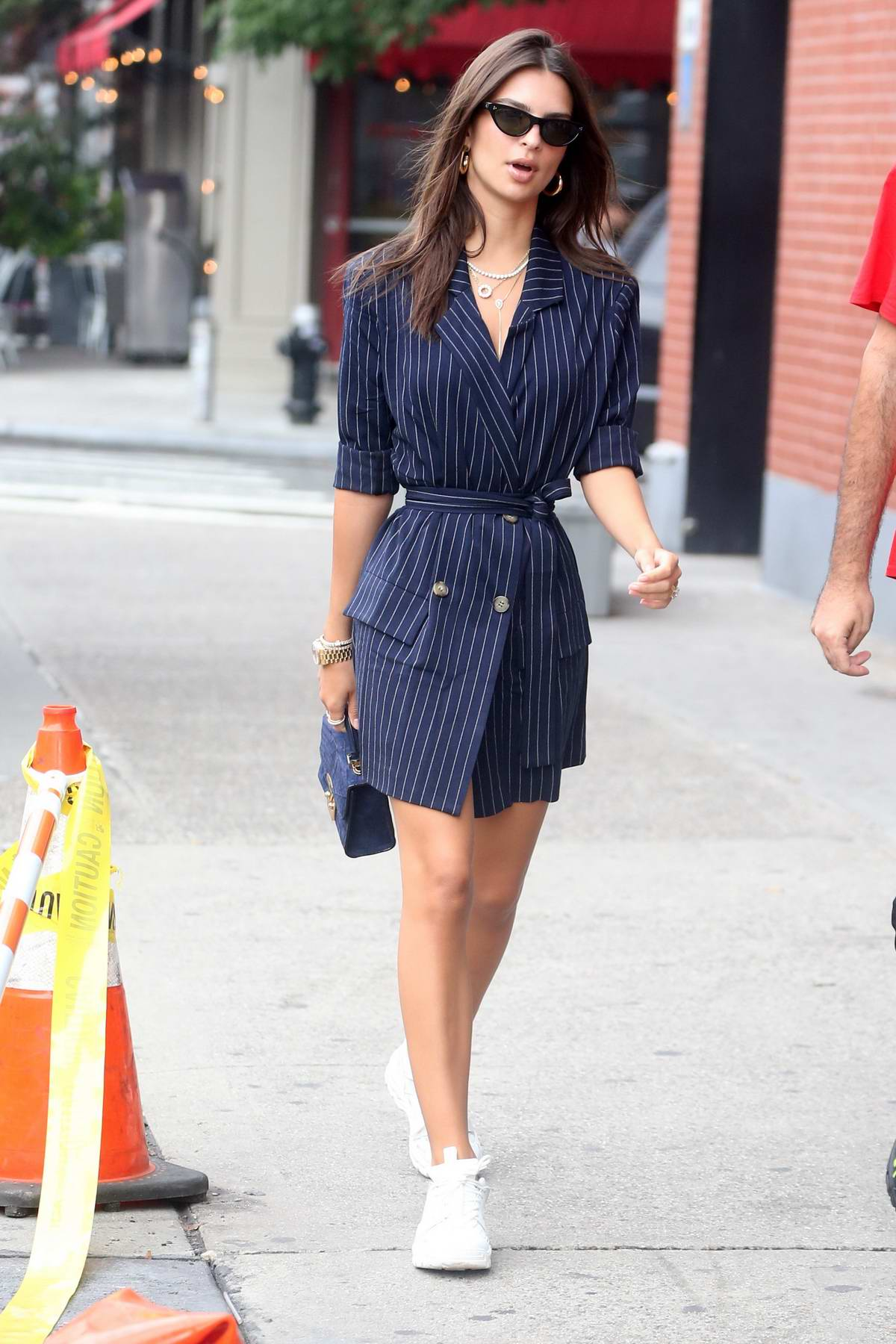 Emily Ratajkowski wears a blue and white pinstriped robe dress with white sneakers while out with a friend in New York City
