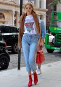 Gigi Hadid rocks brown sweater and cropped jeans with red boots to match her handbag as she leaves her SoHo apartment in New York City