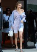 Gigi Hadid steps out of her apartment in an oversized blue shirt with white biker shorts as she heads out in New York City