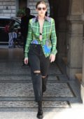 Gigi Hadid steps out wearing ripped jeans and an unbuttoned green plaid shirt during Milan Fashion Week in Milan, Italy