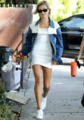 Hailey Baldwin wears a denim jacket over a white mini dress as she heads to a meeting with a friend in West Hollywood, Los Angeles