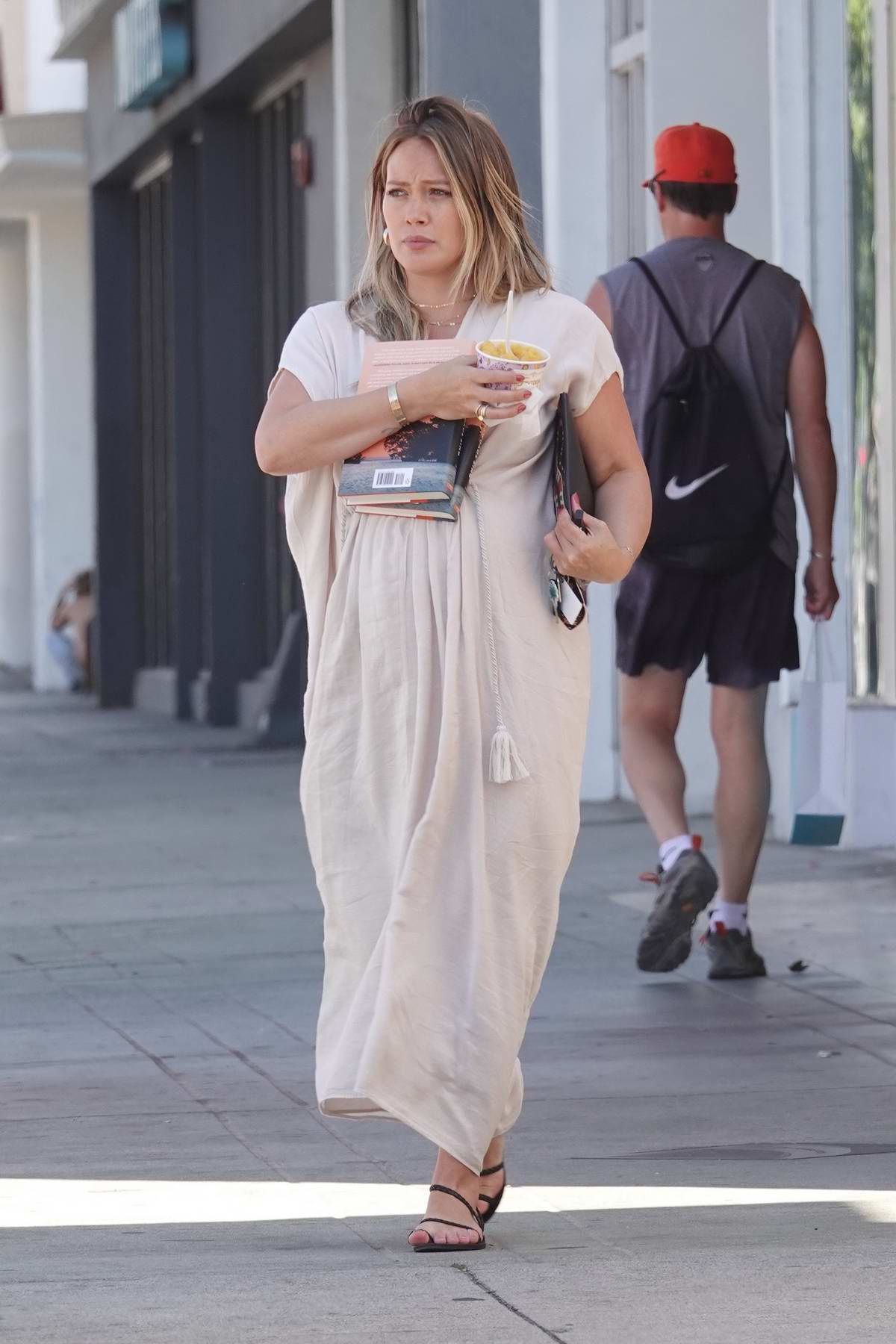 Hilary Duff juggles her frozen fruit cup her new 'delia owens' books and her keys while out in Los Angeles