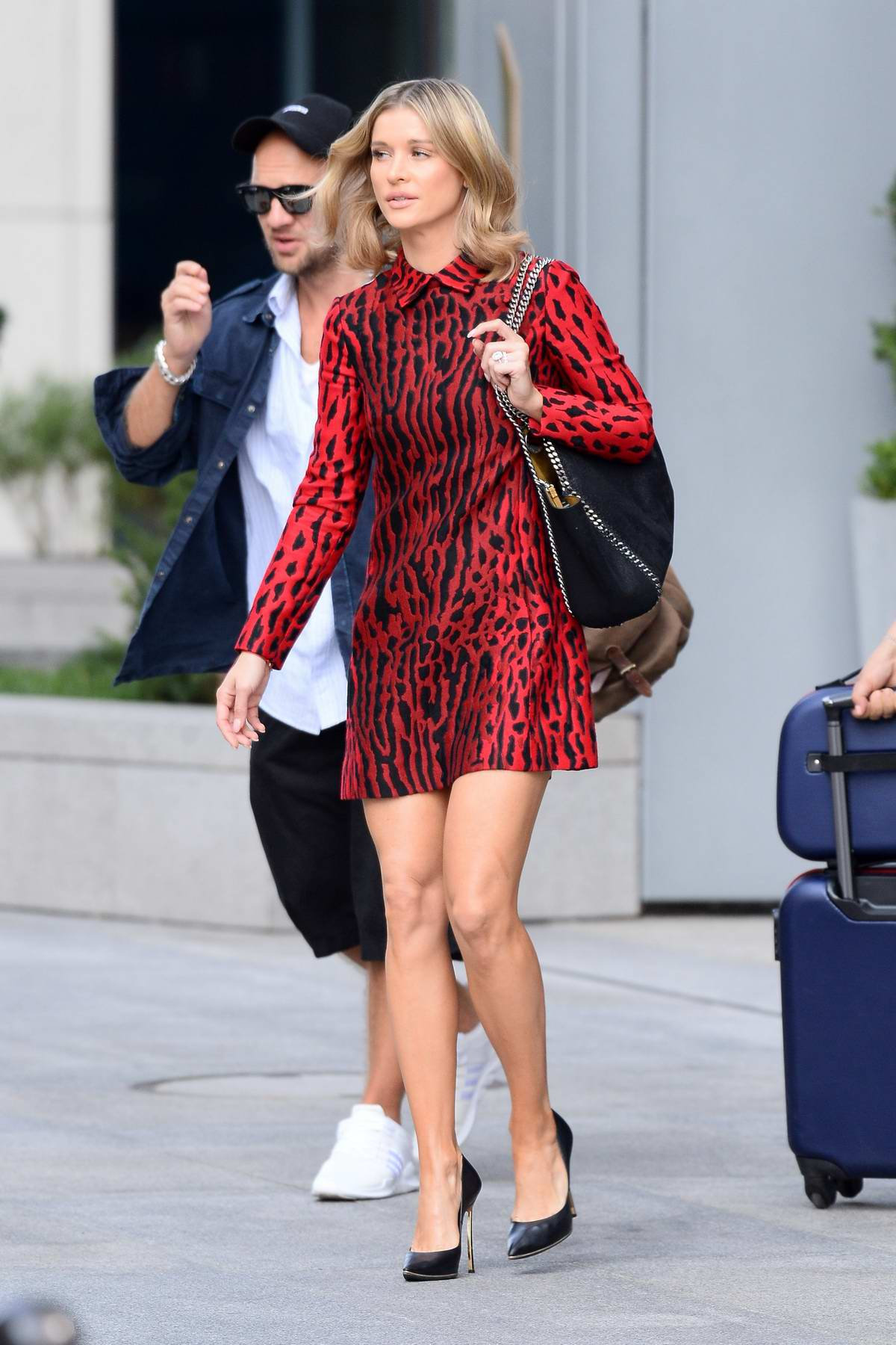 Joanna Krupa wears a red animal print dress as she heads out in Warsaw, Poland