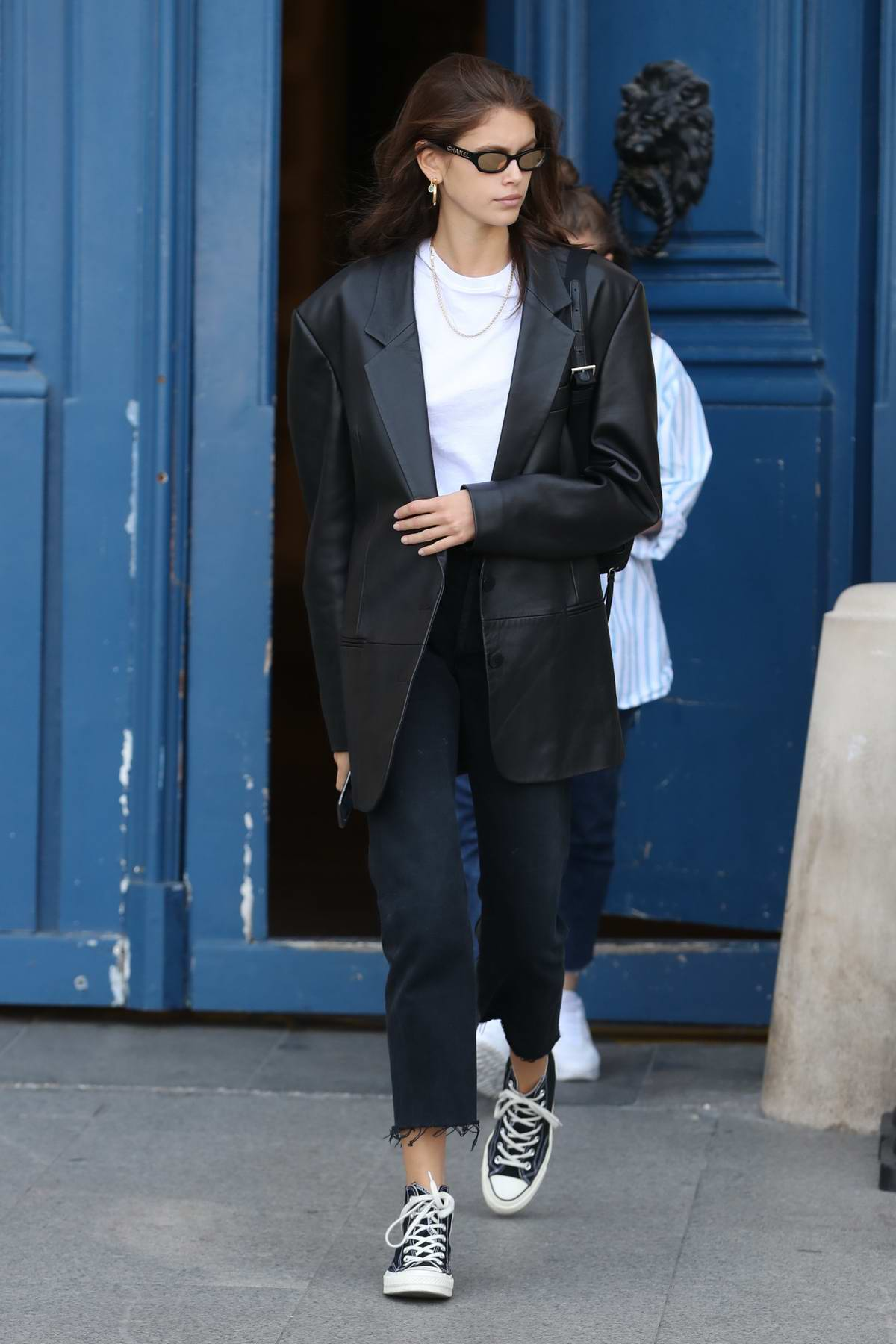Kaia Gerber steps out in a black leather coat over a white top with cropped jeans and converse in Paris, France