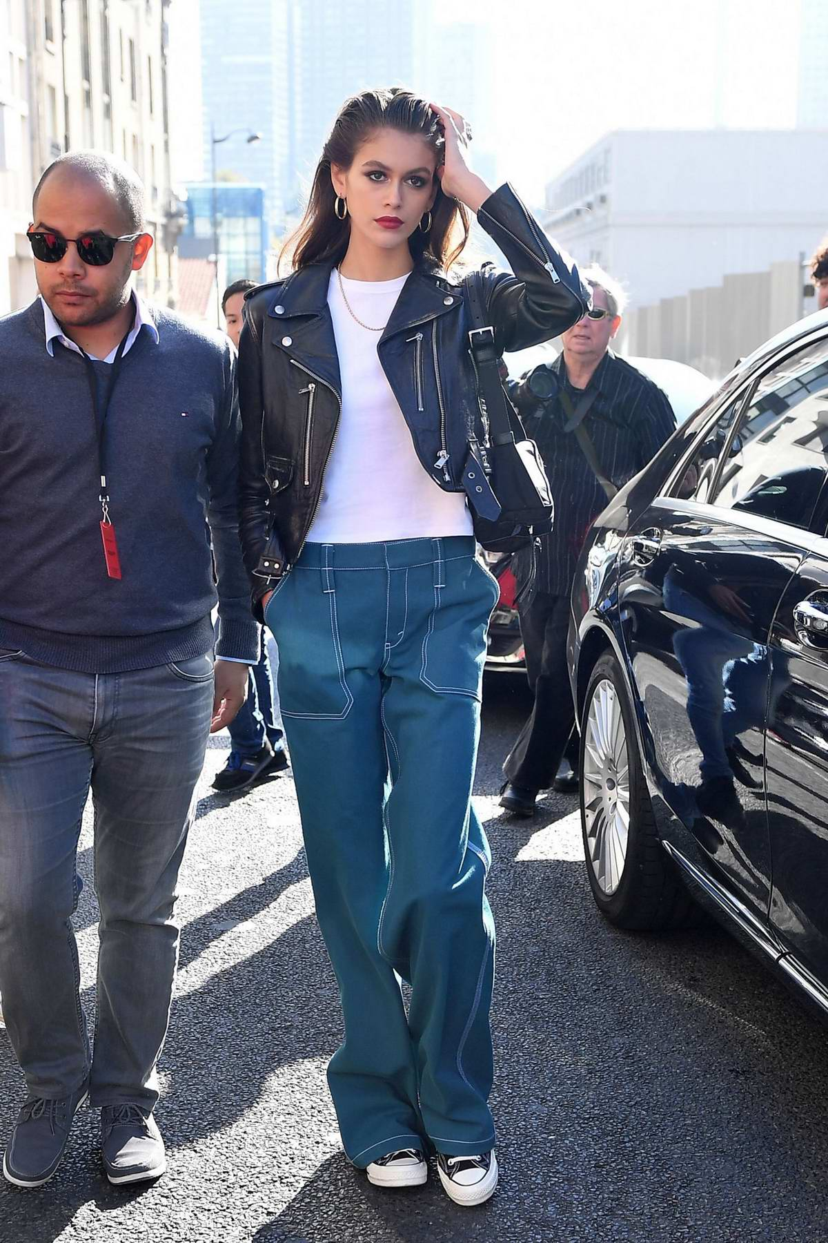 Kaia Gerber steps out in a black leather jacket with wide turquoise pants while out during Paris Fashion Week in Paris, France
