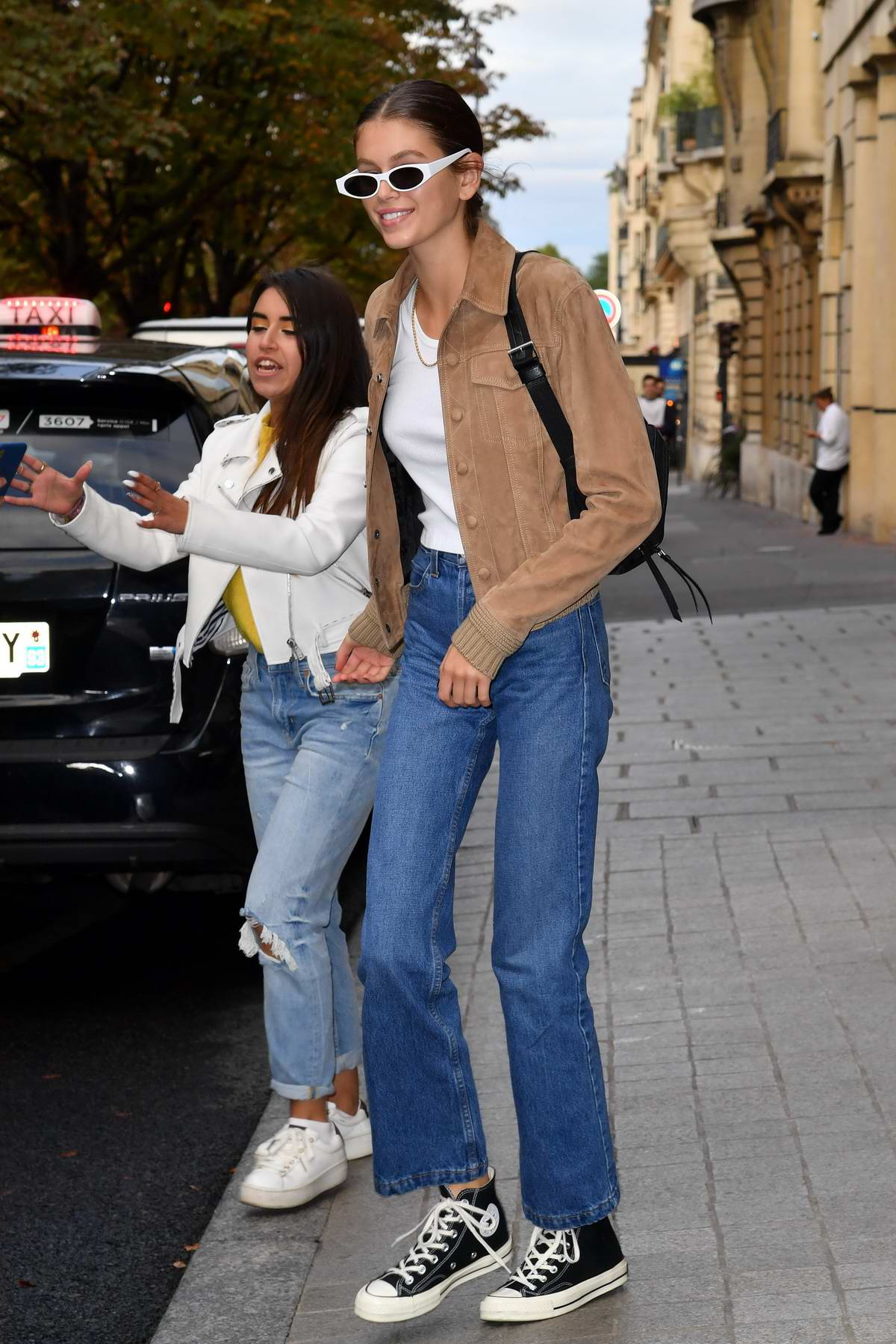 Kaia Gerber wears a brown suede jacket and jeans as she leaves her hotel in Paris, France
