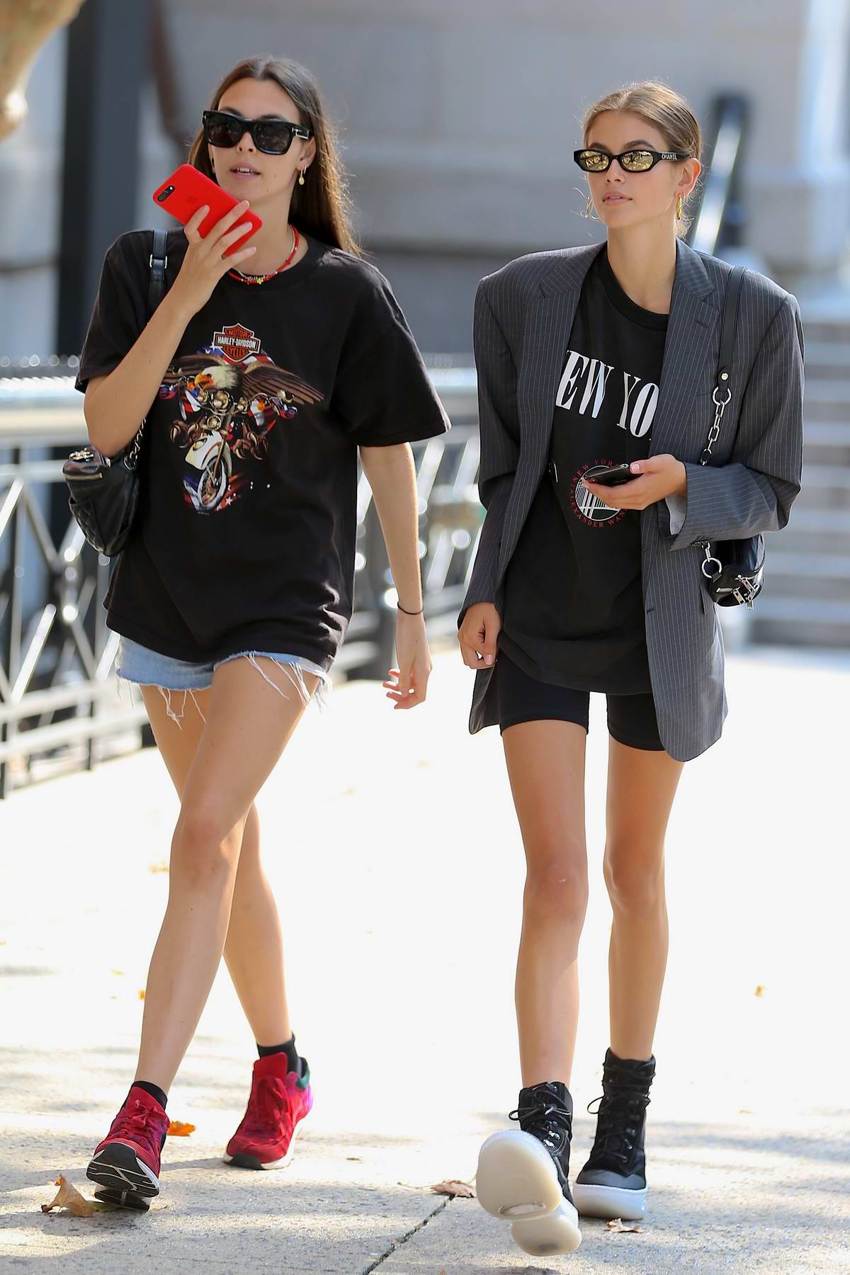 Kaia Gerber wears grey blazer over a black tee with biker shorts while out with Vittoria Ceretti in SoHo, New York City