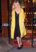 Karlie Kloss heads out in a black dress and yellow long coat in Paris, France