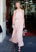 Karlie Kloss wears a light peach dress as she leaves the Royal Monceau Hotel during Paris Fashion Week in Paris, France
