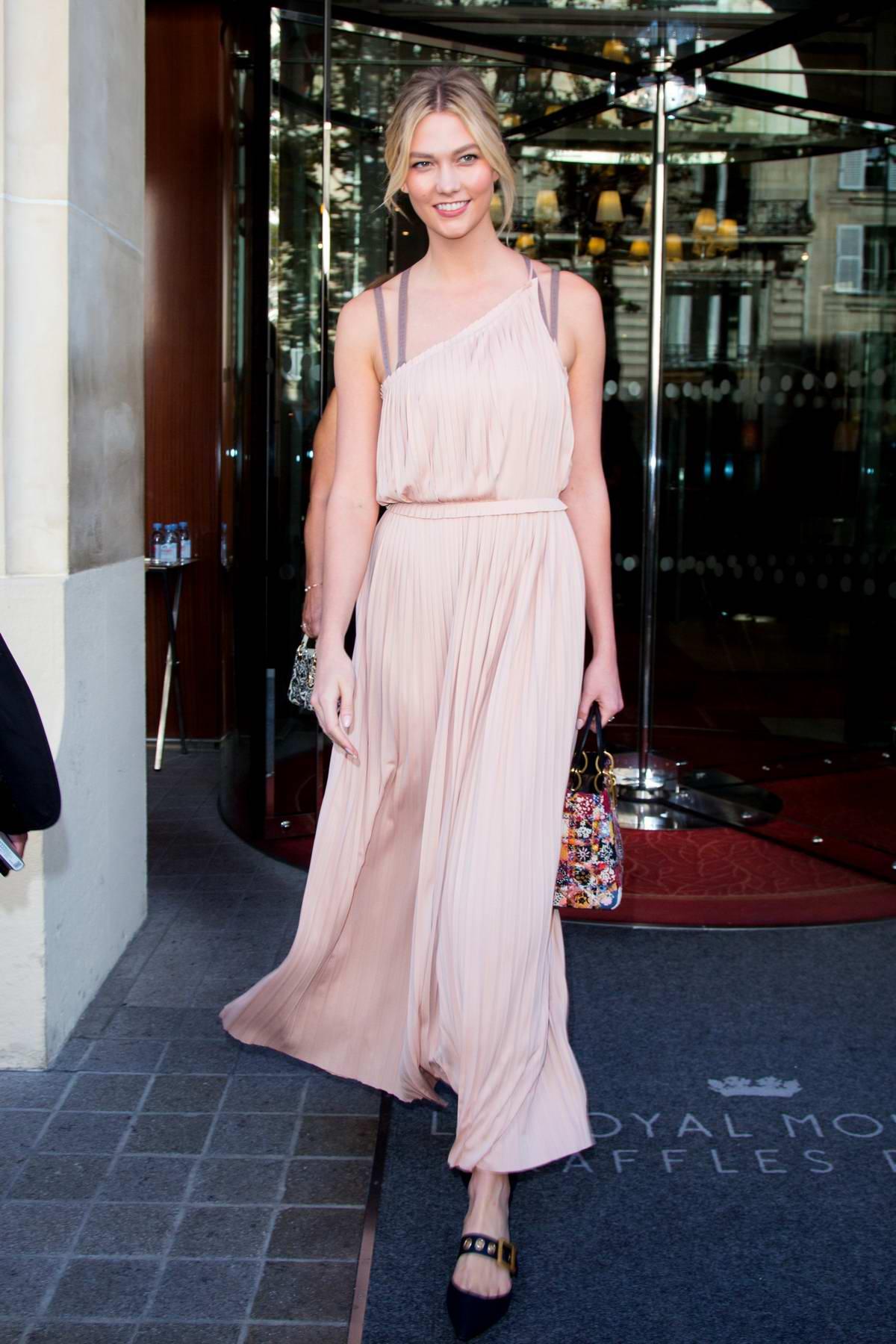 Karlie Kloss wears a light peach dress as she leaves the Royal Monceau Hotel during Paris Fashion Week in Paris, France
