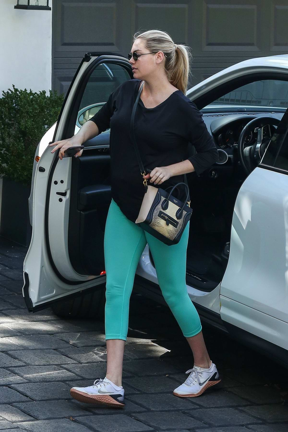 Kate Upton hits the gym in a black top and coral green leggings in Los Angeles