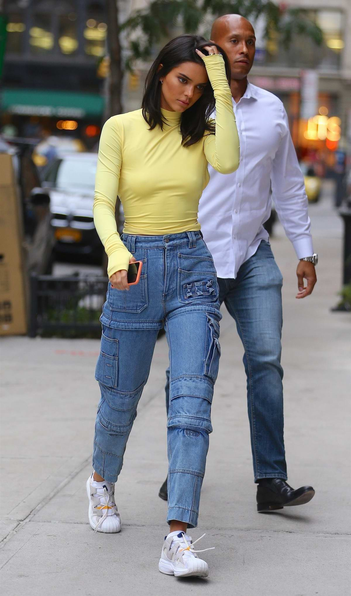 Kendall Jenner seen wearing a neon top with high waisted jeans and sneakers as she leaves Bar Pitti in New York City