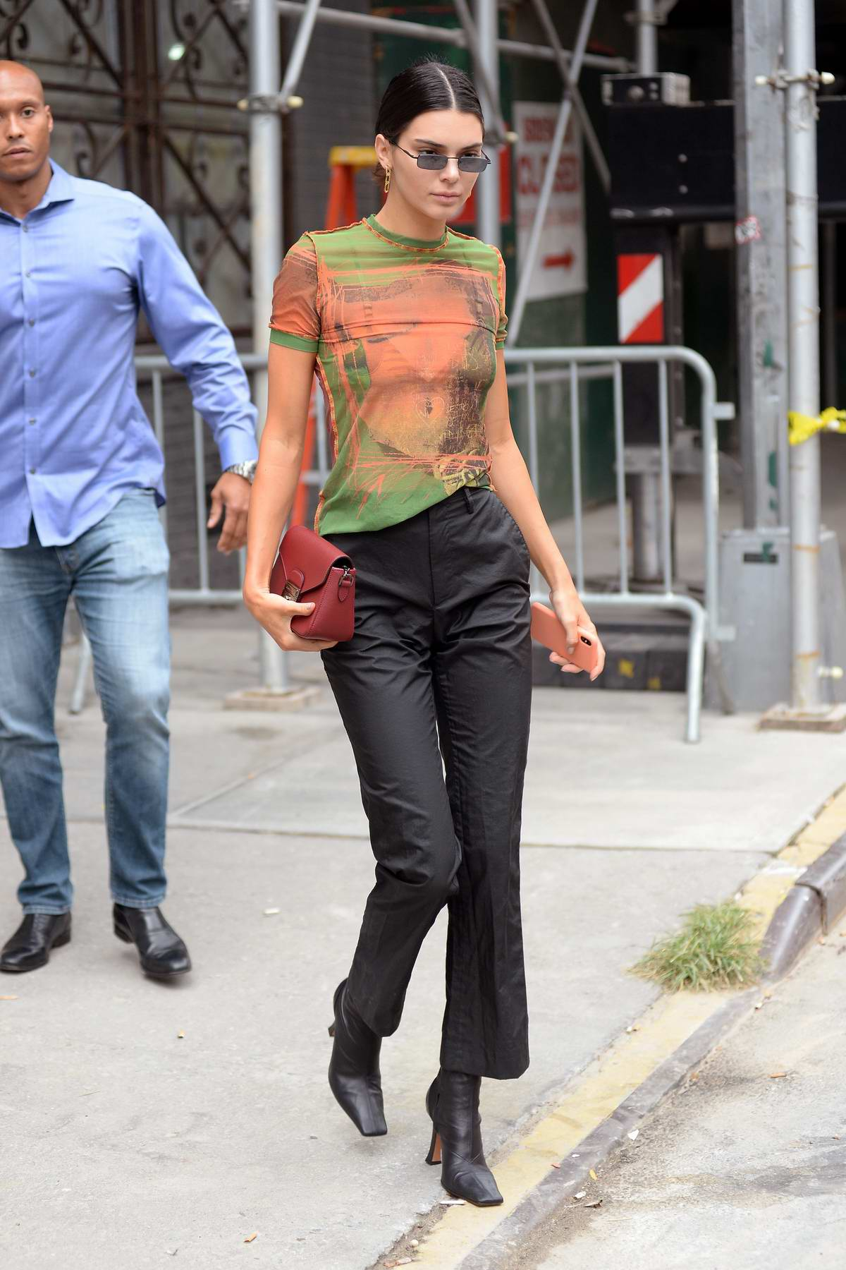 Kendall Jenner stepped out in a patterned sheer top and black trousers with black boots in New York City
