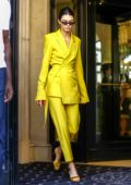 Kendall Jenner steps out of her hotel wearing a bright yellow suit during Paris Fashion Week in Paris, France