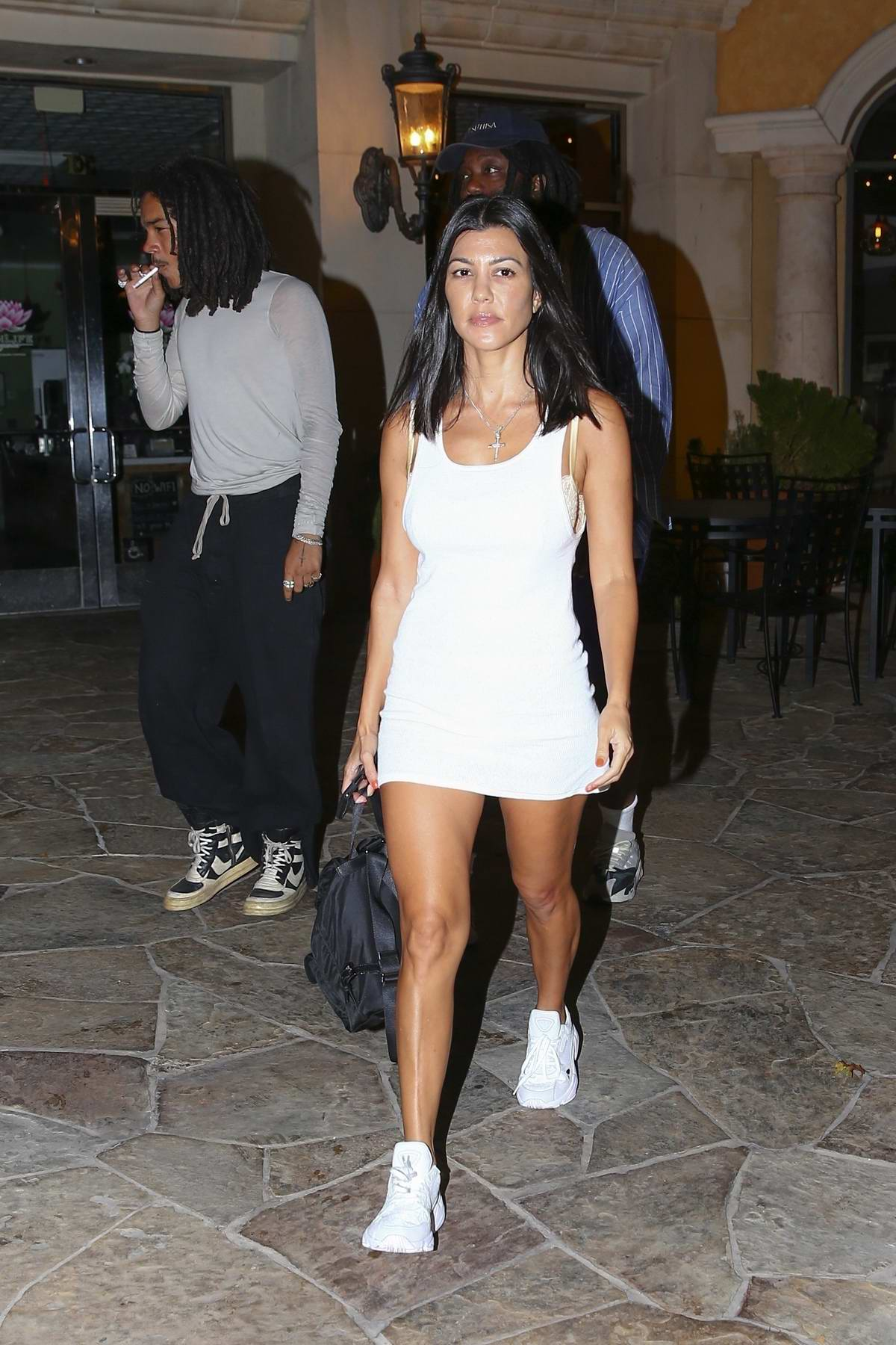 Kourtney Kardashian wore a short white dress as she leaves Sugarfish during a night out with Luka Sabbat in Los Angeles