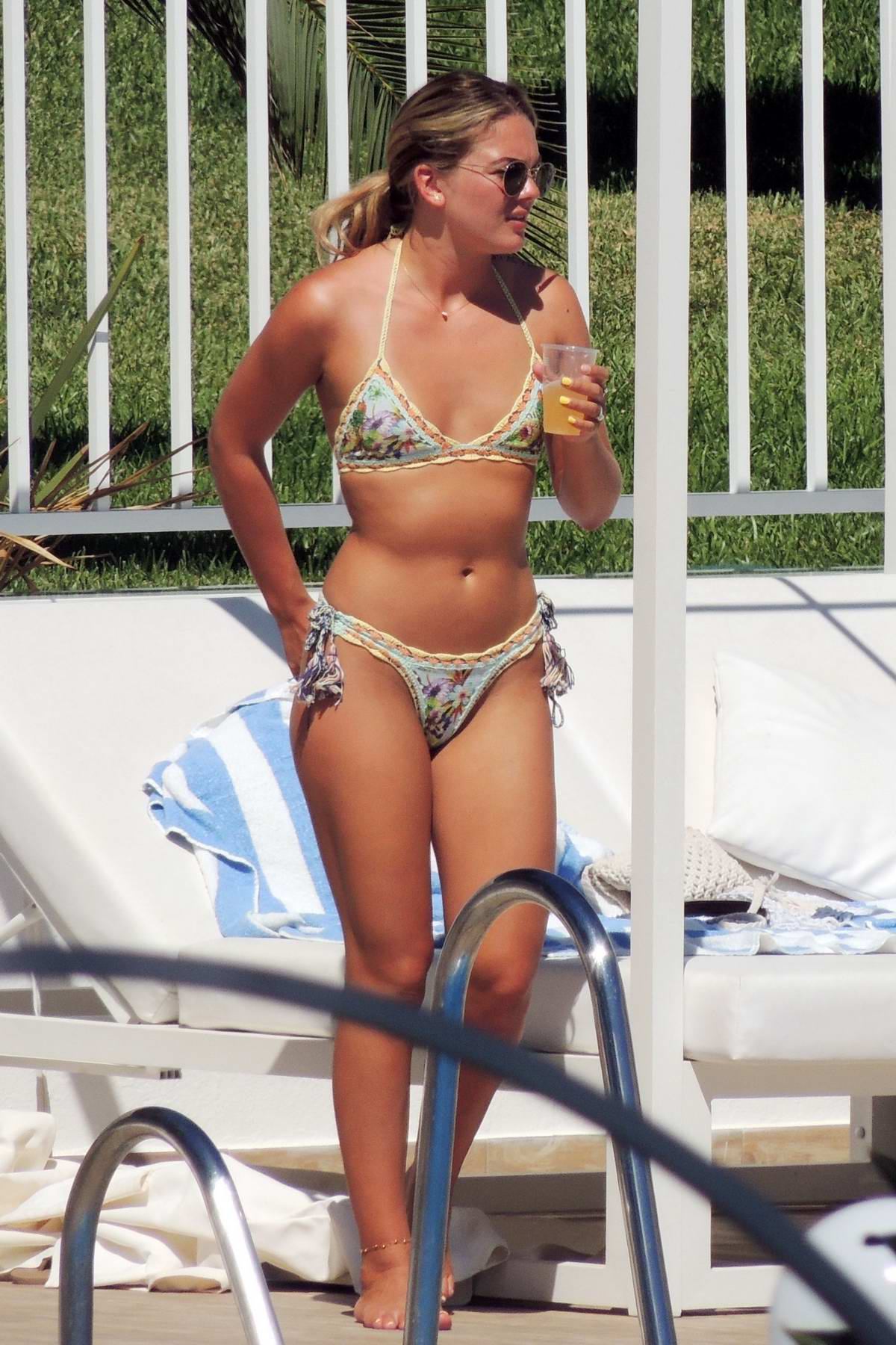 Louisa Johnson wears a floral print bikini while relaxing by the pool with her new boyfriend in Marbella, Spain
