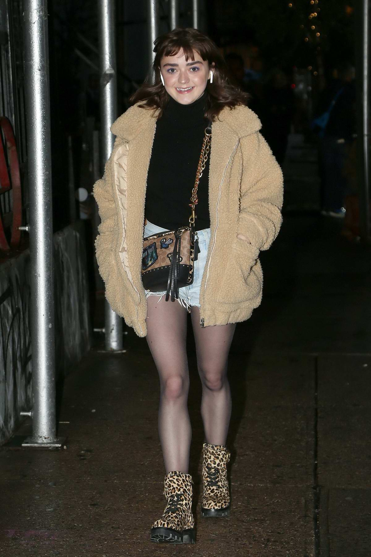 Maisie Williams is all smiles as she steps out in beige sherpa jacket and denim shorts with leopard print boots in New York City