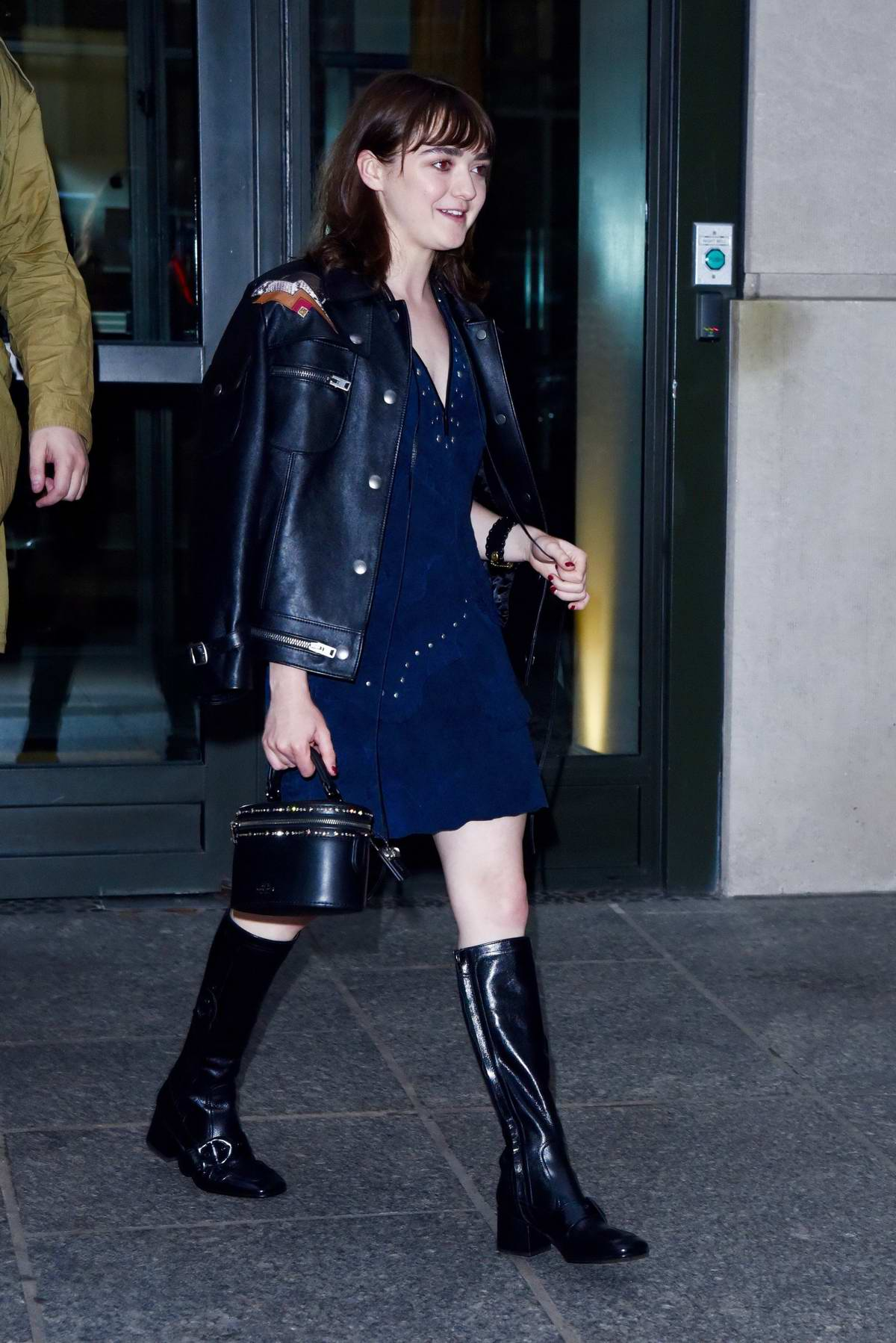 Maisie Williams spotted in black leather jacket over a blue dress with knee high black boots while out in New York City